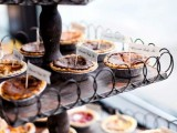a rustic industrial pie bar of metal and plywood, with mini pies and tags on them is a cool and cozy idea for a rustic wedding