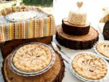 a rustic boho wedding with wood slices, a box with plates and a colorful towel and tasty pies and a wedding cake with a topper