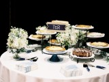 an elegant summer wedding pie bar with white blooms and greenery, a chalkboard sign, napkins and delicious pies is perfect for a boho wedding