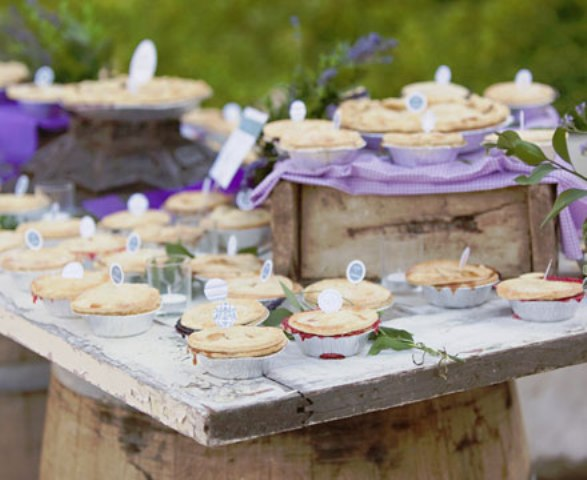 a lovely spring or summer wedding pie bar with crate and box stands, lilac linens, greenery and mini pies with toppers is a lovely and chic idea