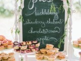 a simple vintage pie bar with a chalkboard sign decorated with greenery and blooms and with various stands with pies is a cool and lovely idea