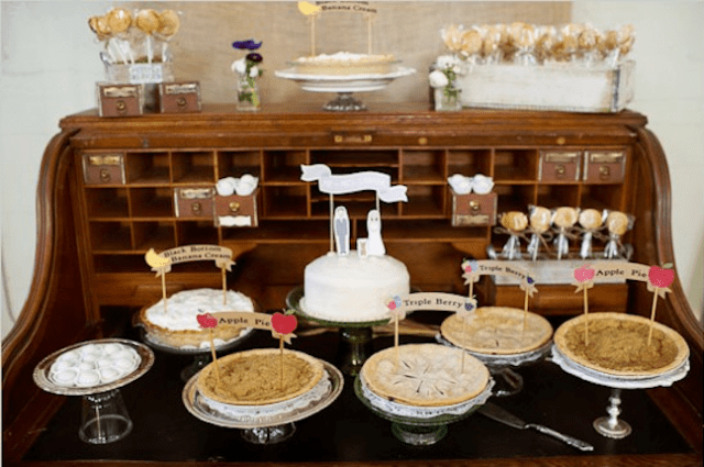 a vintage pie bar of a vintage buffet, with popsicles, a wedding cake and lots of delicious pies plus some wildflowers