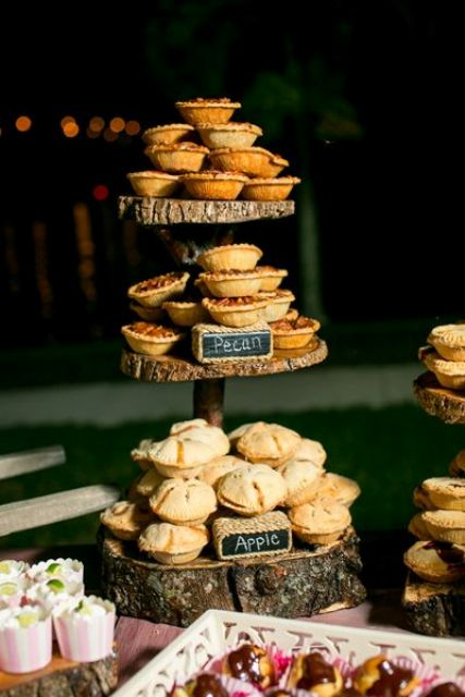 a rustic pie stand of wood slices and with chalkboard marks plus delicious pies of all kinds