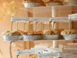 a pie stand with lots of pies and marks on them is a simple and cool idea for a modern wedding, cozy up your guests
