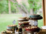 a rustic pie bar with wood slice stands, a burlap runner, some pebbles and greenery and blooms is ideal for any rustic or farmhouse wedding