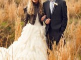 a vintage-inspired look with a black suit, a blue shirt and a black tall hat plus a boutonniere