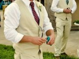 a cowboy-inspired groom's look with neutral pants and a waistcoat, a white shirt, a burgundy tie and a white hat