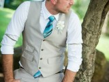 a neutral waistcoat and pants, a white shirt, a turquoise tie and a grey hat