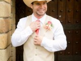 a cowboy-inspired groom's look with jeans, a white shirt, a neutral waistcoat, a coral tie and a cowboy hat