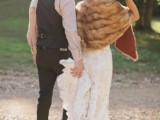 a vintage groom's look with a black waistcoat, pants, a neutral shirt, a brown hat and brown shoes