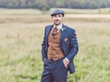 a vintage groom's look with a navy pritned suit, a brown waistcoat, a tie and a grey cap