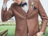 a vintage-inspired groom's look with an ocher waistcoat and jacket, red pants, a striped shirt, a navy bow tie and a brown hat