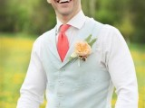 a bright vintage-inspired groom's outfit with tan pants, a white shirt, a mint green waistcoat, a printed cap