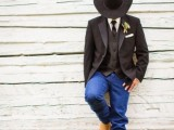 a rustic groom's look with jeans, a black waistcoat and jacket, a black hat and tie and a white shirt