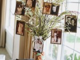 blooming branches in a whimsy vase with leaves and blooms plus vintage family photos on them for a spring wedding