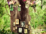 a real tree with family photos on them and bright blooms in jars hanging down from the tree