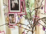a whimsy tree of branches with photos in bright frames, beads and crystals, put into a vase with moss