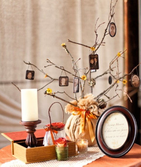blooming branches with family photos put into a vase wrapped with fabric and secured with a bow for a fall wedding