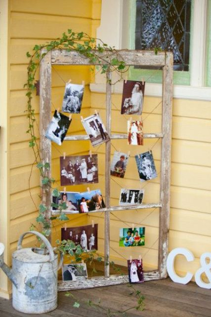 a rustic shabby chic window frame with greenery and family photos is a cozy substitute for a family tree
