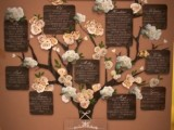 a vintage rustic family tree of plywood attached to the wall, with fabric blooms and leaves and plywood cards with names