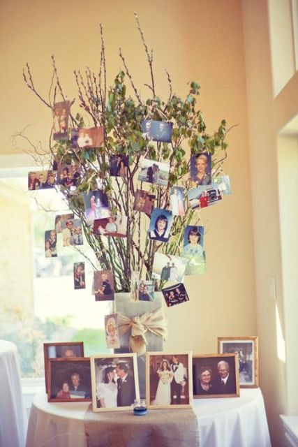 a quirky family tree made of a vase wrapped with fabric, with branches with green leaves and family photos on them
