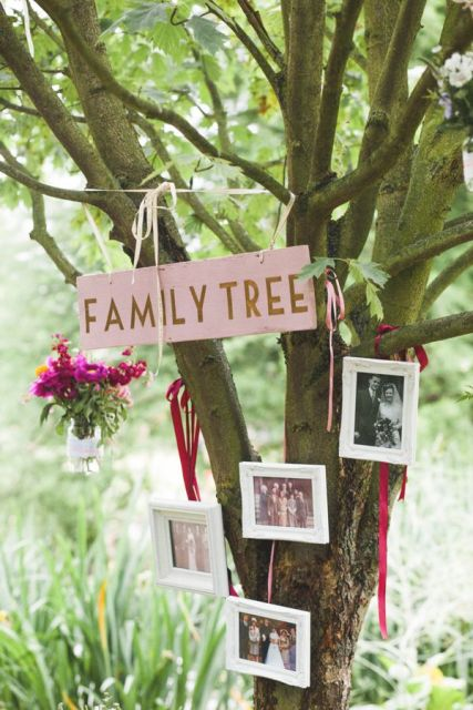 a real tree with a sign and some family photos plus blooms in a vase hanging down is a cozy and natural idea