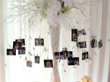 a quirky family tree of a vase wrapped with printed paper, lush white blooms and branches plus family photos hanging down from them