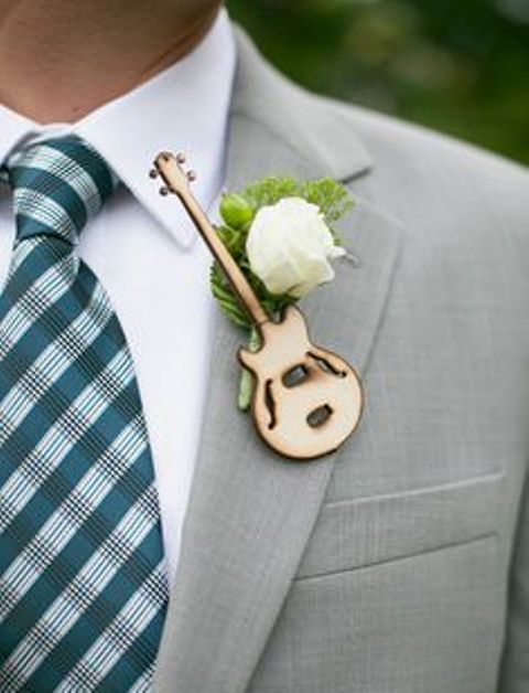 a wedding boutonniere of a wood burnt guitar, a white bloom and greenery for a music-loving groom