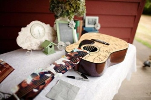 a guitar with photos as a wedding guest book is a very functional and cool idea for a wedding