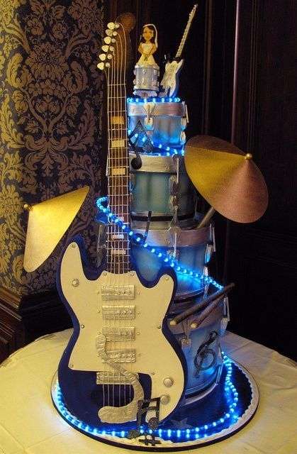 a jaw-dropping wedding cake with a guitar, umbrellas, lights and funny cake toppers is a very cool idea