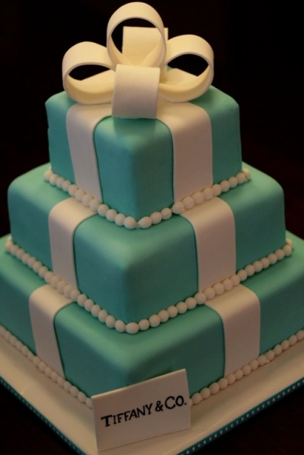 a tiffany blue wedding cake imitating a gift box from tiffany with white ribbons and a large sugar bow on top is a creative idea