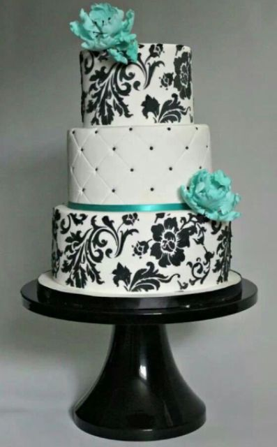 a black and white wedding cake with beads and flroal patterns and tiffany blue sugar blooms will highlight your wedding color scheme