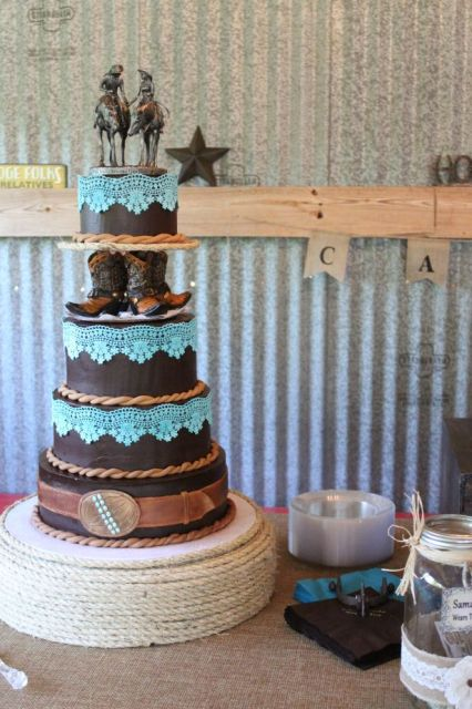 a whimsical chocolate wedding cake decorated with ribbons, tiffany blue lace, cowboy boots and unique toppers