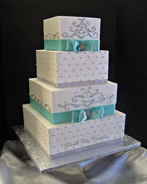 a white wedding cake with edible metallic embellishments and tiffany blue ribbons and bows