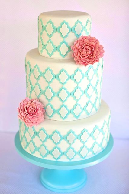 a white wedding cake with tiffany blue patterns and coral blooms is a bright and cheerful option for summer