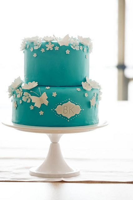 a tiffany blue wedding cake with white sugar butterflies and flowers plus monograms