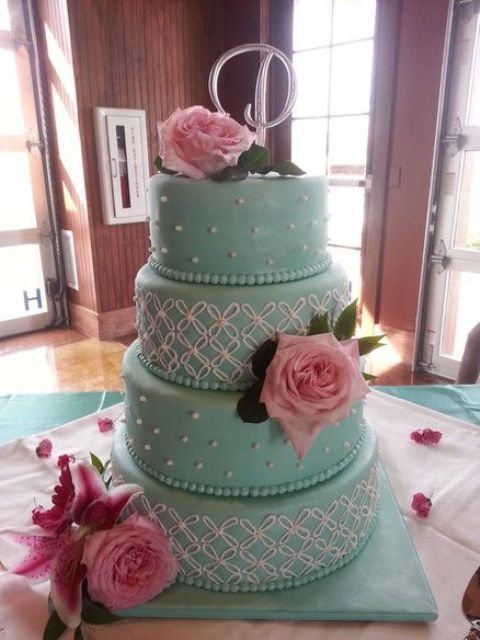 a romantic tiffany blue wedding cake with white patterns and beads, pink roses and a pretty topper
