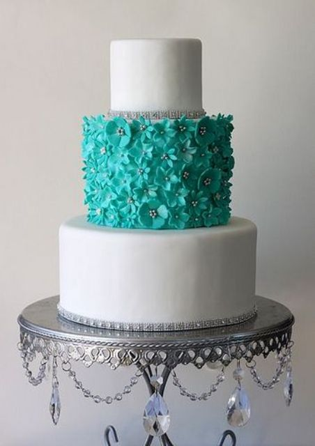 a chic white and tiffany blue wedding cake with sleek tiers, a floral tier and some embellishments