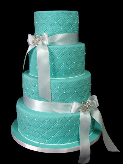 a patterned and textural tiffany blue wedding cake decorated with beads and ribbon bows