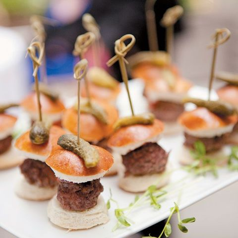 a white tray with greenery and mini burgers on skewers is a cool idea for a modern wedding