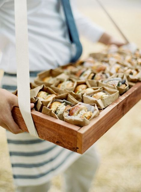 a wooden box with burgers in paper bags to comfortably serve them and eat them