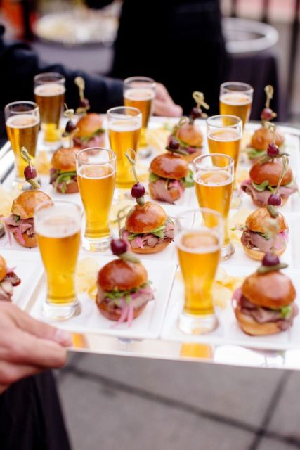 a silver tray with mini burgers with olives and salami on skewers and mini beer glasses
