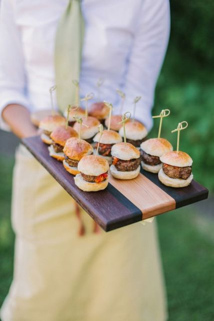 a striped wooden tray with burgers on skewers is a comfy and stylish way to serve them