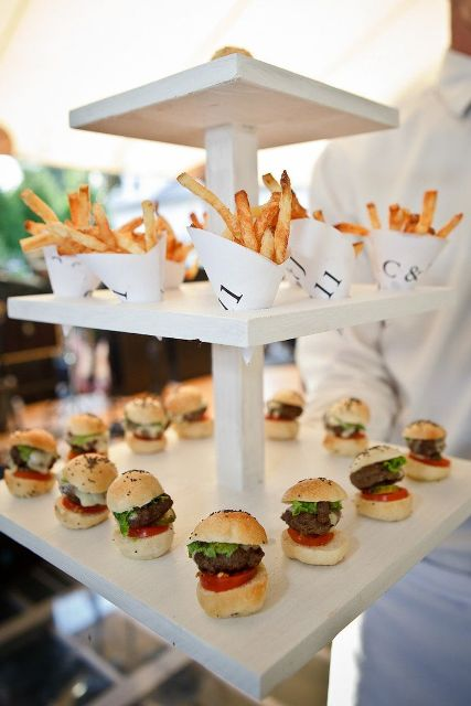 a modern stand with mini burgers and paper cones with French fries is a perfect wedding food station for a modern casual wedding
