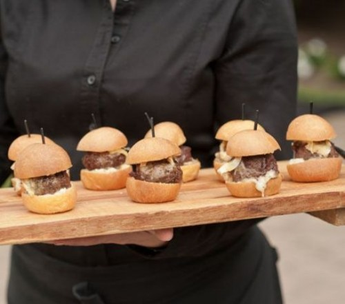 a wooden tray with burgers and skewers is a cool idea for a modern wedding that isn't too formal