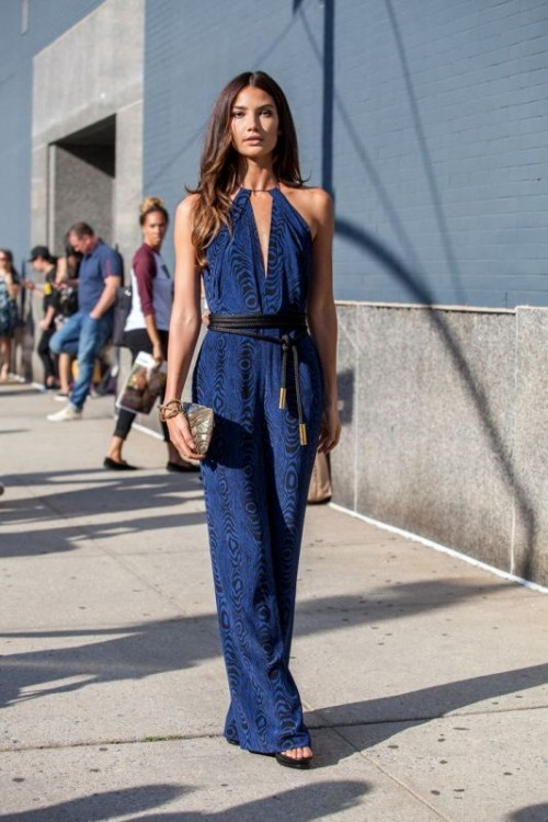 a navy print jumpsuit with a deep neckline, no sleeves and wideleg pants, a black rope sash and acool shiny clutch