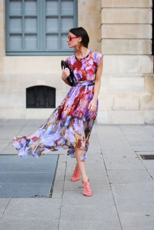 a sleeveless flowy midi watercolor dress in lots of shades, a black clutch and red shoes