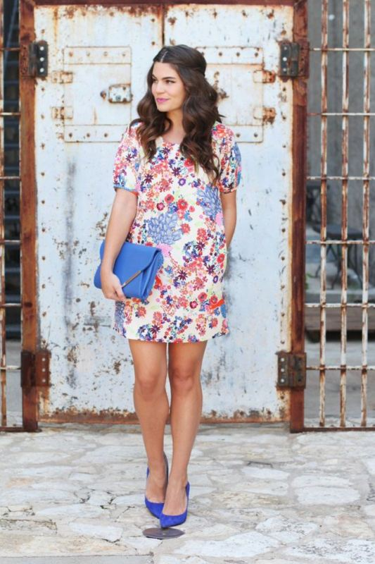 a bright and short floral dress with short sleeves, blue shoes and a matching clutch for a bold look