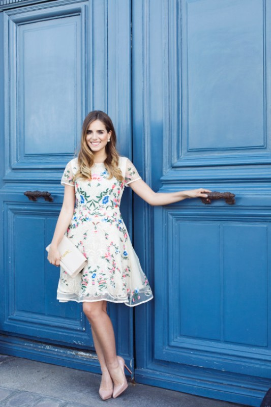 a pastel mini dress with floral prints, a high neckline, short sleeves, nude shoes and a white clutch
