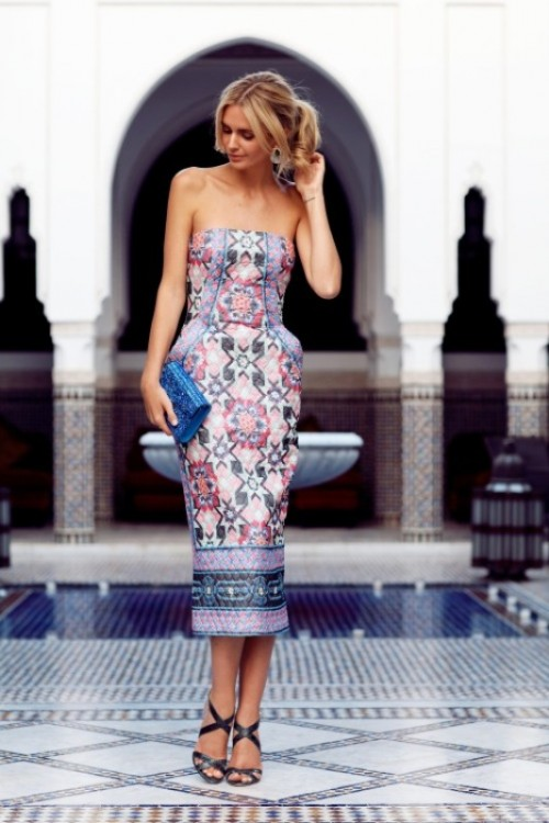 a catchy strapless printed dress, a bright blue clutch and black strappy shoes for a Moroccan spring wedding